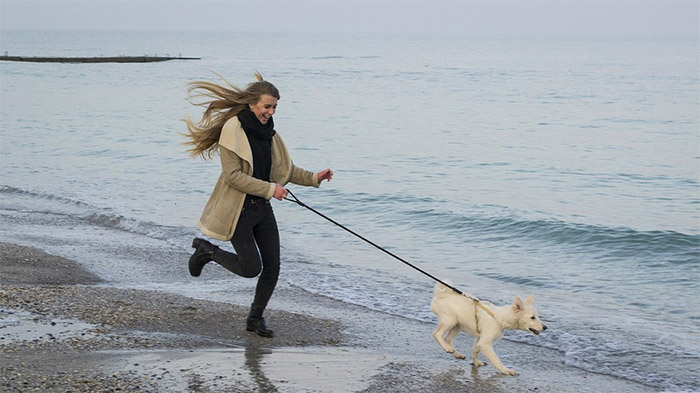 lady running down the beach with a dog